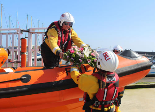 Wreaths are passed onto the lifeboat before being taken out to sea