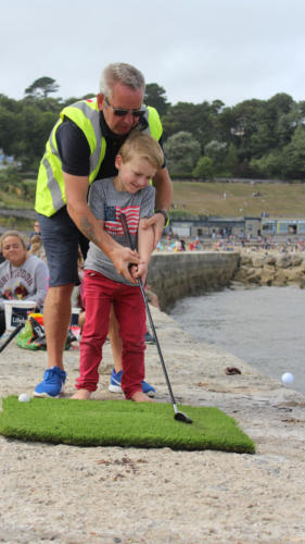 Lifeboat crew member Dave Holland gives some tips to Noah Turner in the Hole in One competition