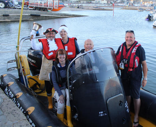 Lord Julian Fellowes aboard the harbourmaster's launch with wife Emma, mayor Michaela Ellis, town crier Alan Vian and lifeboat crew member Mark Colley