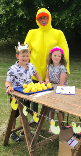 Fete Prince and Princess Seth Buller and Maisie White help John Fowler sell duck race tickets