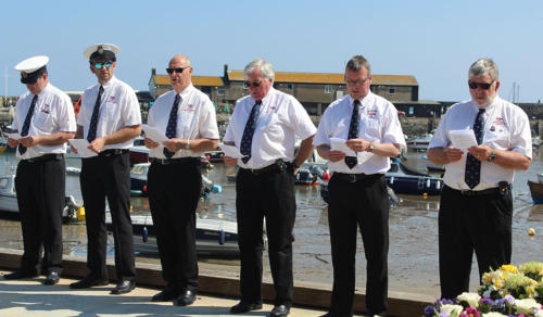 Members of Lyme regis lifeboat crew line the slipway for Blessing of the Boats