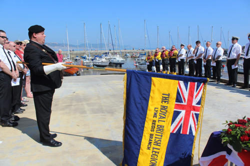 Royal British Legion standard bearer lowers the standard during the National Anthem