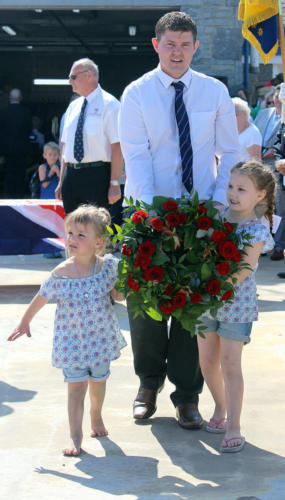 Daniel Buckley from the Lyme Regis branch of the Royal British Legion is accompanied by his daughters Brooke and Faith as he carries a wreath down the slipway