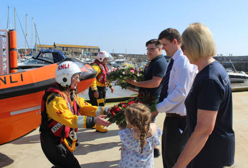 Representatives from Lyme's seafaring organisations and the Royal British Legion pass wreaths to members of the lifeboat crew